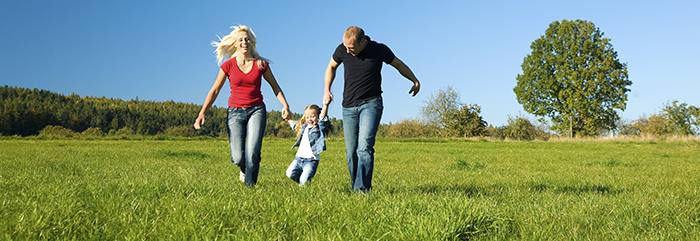 Photo: parents running across a field with a child between them